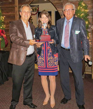 Previous recipient Paul Spriet of Grand Bend Motorplex presents the 2015 award to Doug and Cathy Ellison of Ellison Travel & Tours