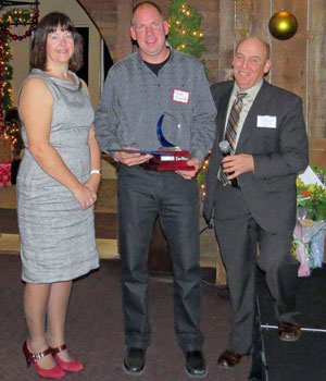 Chamber Manager Susan Mills and Past-President Glen Baillie present the 2015 Phyllis Statchuk Customer Service Excellence Award to Mike Stanlake.